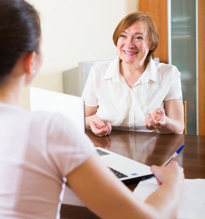 Feliz mujer responder a las preguntas del trabajador social en casa Foto de archivo