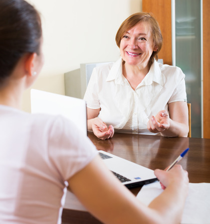 Happy woman answer questions of social worker at home