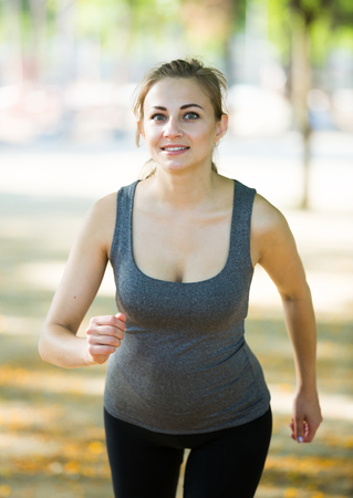 Young happy american female in sportwear running in the sunny park