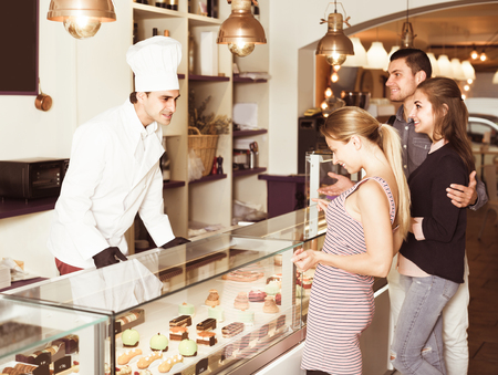 fmale: Cheerful pastry chef fmale is serving visitors in cozy pastry shop Stock Photo