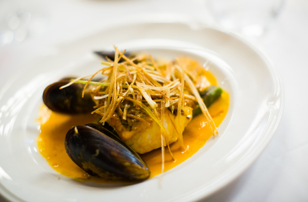 baked white fish with mussels on a plate, close up Stock Photo