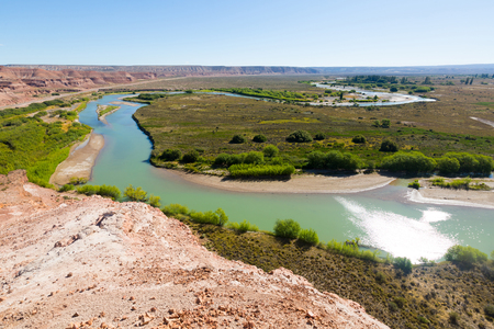 steep: Hilltop view of river and green plain near Paso de Indios in Patagonia area in Argentina Stock Photo