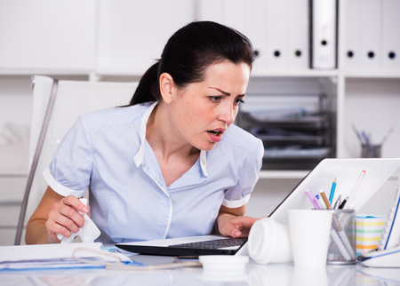 Portrait of office female have problems at work near the laptop