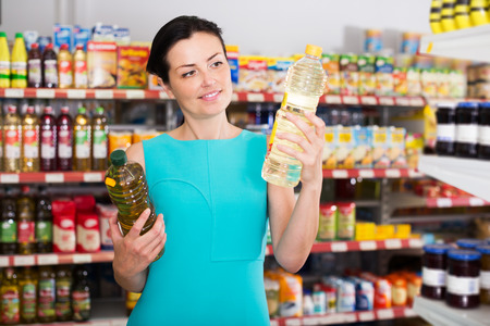 store shelf: Glad young woman choosing different oil in bottle at the supermarket Stock Photo