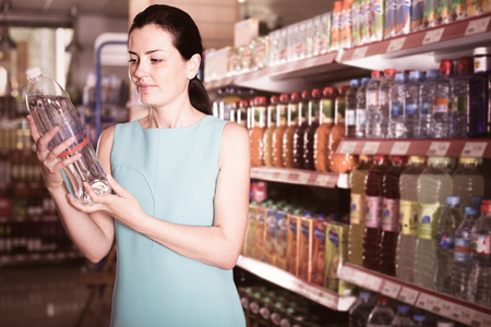 store shelf: Portrait of adult woman choosing water in bottle at the supermarket