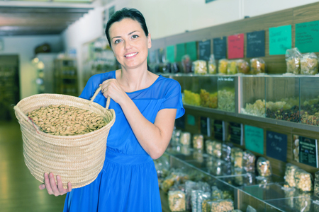 brazilian ethnicity: Smiling cheerful positive adult girl displayed large shopping bag with nuts and smiling in biofood market