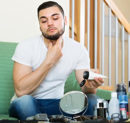 man applying facial cream at home