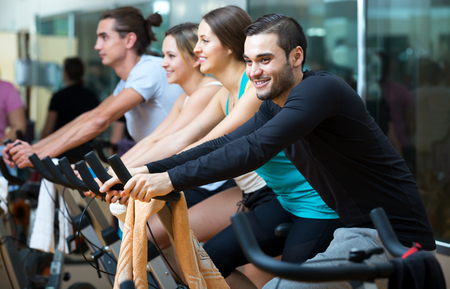 Positive adult men and women riding stationary bicycles in fitness club