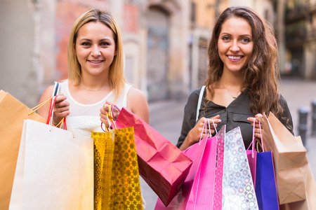 Two joyful young girlfriends holding many bags after shopping