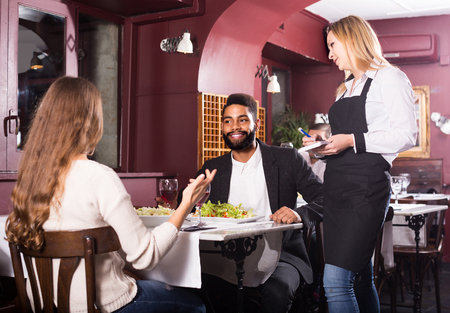 out of date: smiling russian waitress serving meal for young couple at table Stock Photo