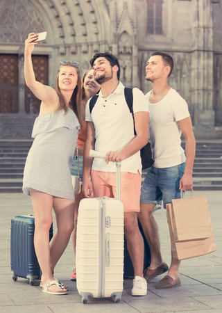 chasing: friendly adult tourists taking selfie on camera in smartphone in European city