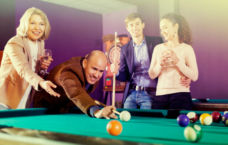 Group of cheerful friends playing billiards and smiling in night club Stock Photo