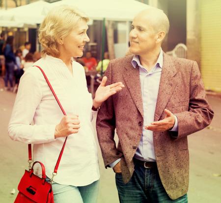 argumentation: glad senior couple talking and taking promenade together outdoors