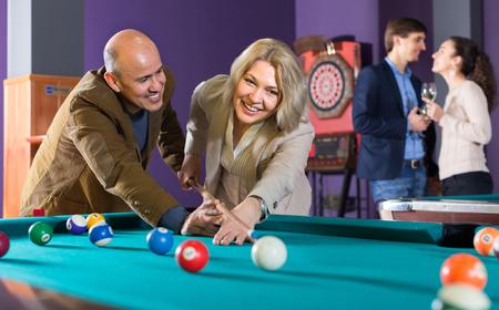 Positive ordinary people having pool game in billiard club