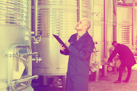 portrait of mature man in uniform standing and taking off data from equipment in winery