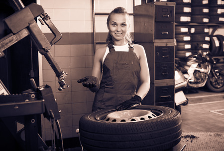 Mechanic woman working on car wheel in service point