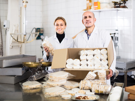 electric material: happy english different aged couple standing with box of turron in production workshop