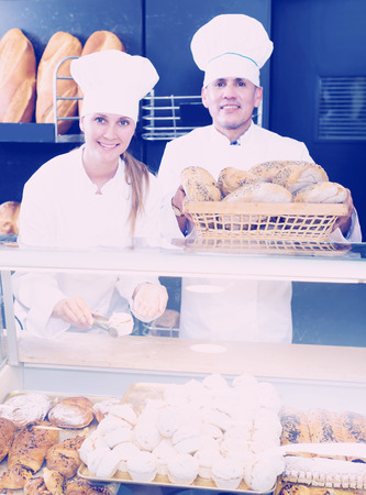 happines: Mature male and young female staff offering fresh baguettes and buns in bakery Stock Photo