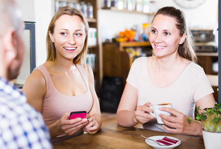 happines: Two happy english girls and one man meeting in cafe and drinking coffee