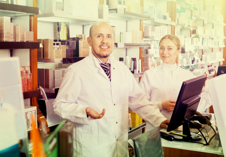 store shelf: Two happy female and male pharmacists in white coats working the pharmaceutical store Stock Photo