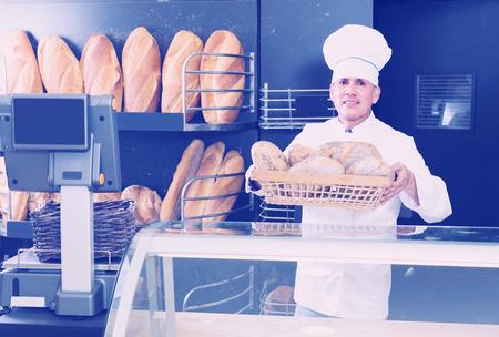 Smiling baker man is showing tasty bread in bakery.