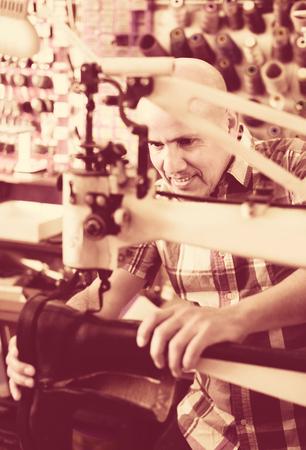 sewing machines: Professional elderly shoemaker stitching footwear on machine in shoe atelier Stock Photo