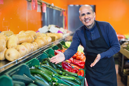 Mature friendly positive seller offering seasonal vegetables in local grocery