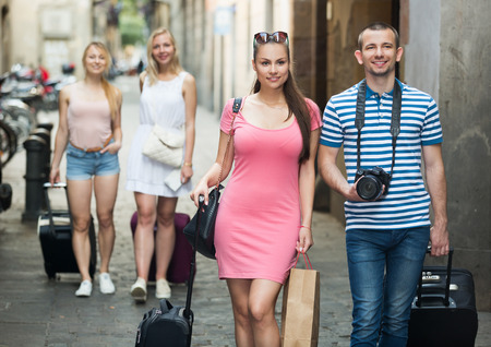 Couple travellers and two friends girls going down european strret with luggage on summer vacation