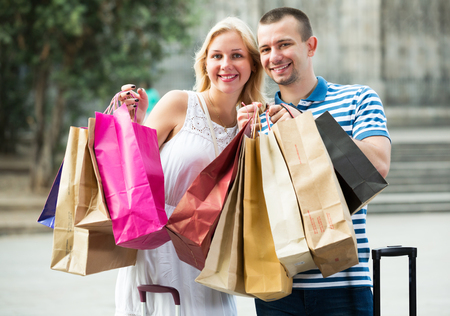 Portrait of young positive couple with many paper shopping bags outdoors
