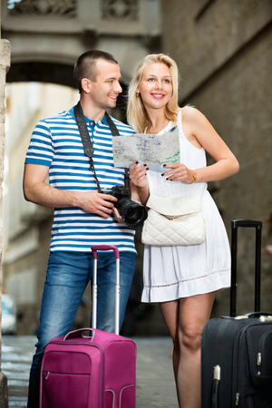 Young cheerful man and positive  woman tourists having map and looking for route in city