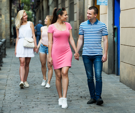 global positioning: Smiling couple walking and looking around in summer city
