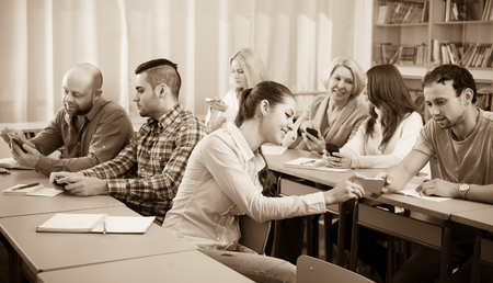 25s: Smiling adult students using smartphones in classroom. Focus on girl Stock Photo