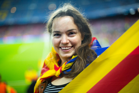 Female football fan 20-30 years old with flag of Catalonia at stadium