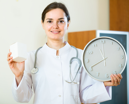 interval: Portrait of smiling female family doctor with big clock