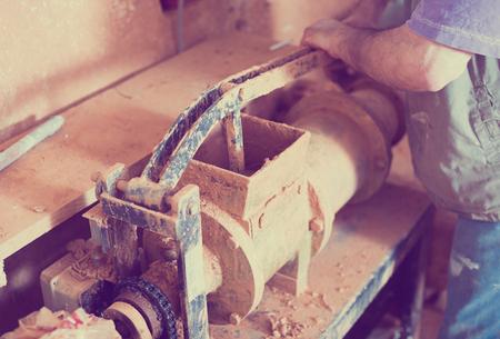 clay forming machine in use in ceramics studio