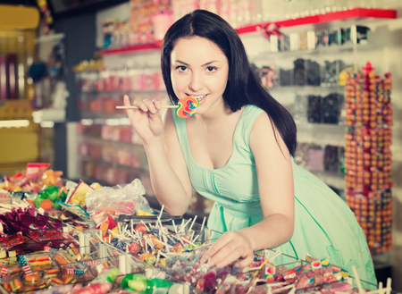 25s: sexy satisfied female posing in the store with lolly on the background of counters with sweets Stock Photo