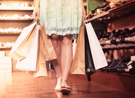 Young woman is going out of the fashion store with full hands of purchases