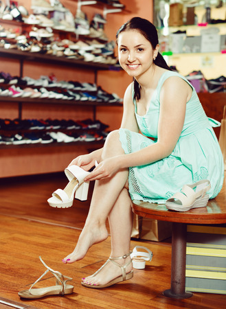 Happy cheerful positive young girl is trying on white heeled sandals for summer season in shoes shop Stock Photo