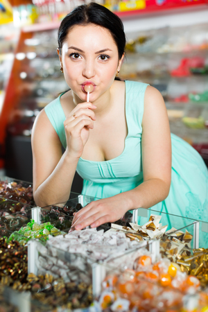 Coquette sexy female posing in the store with lolly on the background of counters with sweets Stock Photo