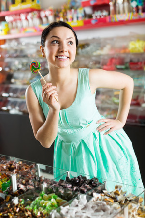 Portrait of smiling shopgirl buying lollipop at sweets store