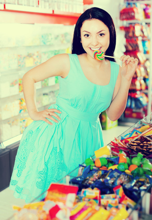 Portrait of young shopgirl with candy at gifts shop Stock Photo