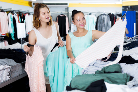 hangers: Smiling young women shopping at the clothing store Stock Photo