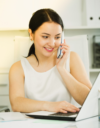 expertize: Smiling female worker talking on phone while working in office Stock Photo
