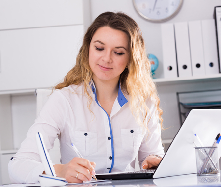 positiv: Young and smiling businesswoman in shirt filling up documents Stock Photo