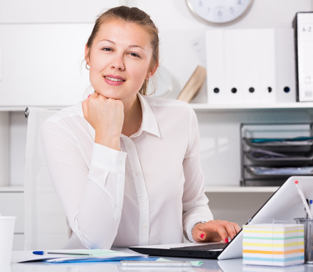 expertize: Young female is posing while working behind laptop in the office.