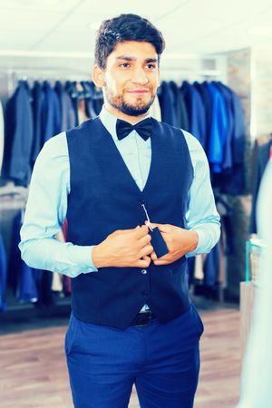 Man is trying on vest in front of the mirror in shop Stock Photo