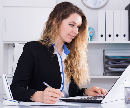 cheerful and smiling woman working in the office at the laptop Stock Photo