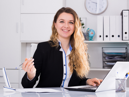 positiv: Young and smiling businesswoman in jacket filling up documents