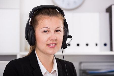 Portrait of dispatcher female in black suit which is talking by headset with client in the office.