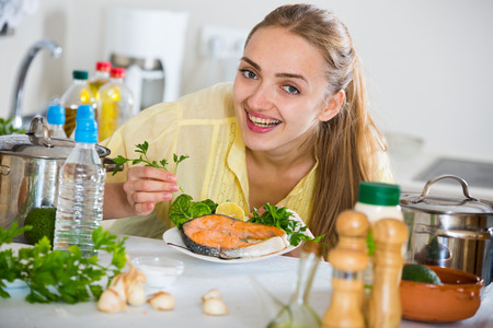 Young female in yellow blouse with cooked salmon at home